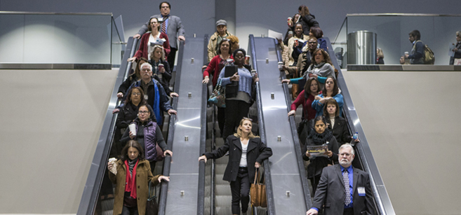 Conference attendees descend on three escalators at the 2018 Conference